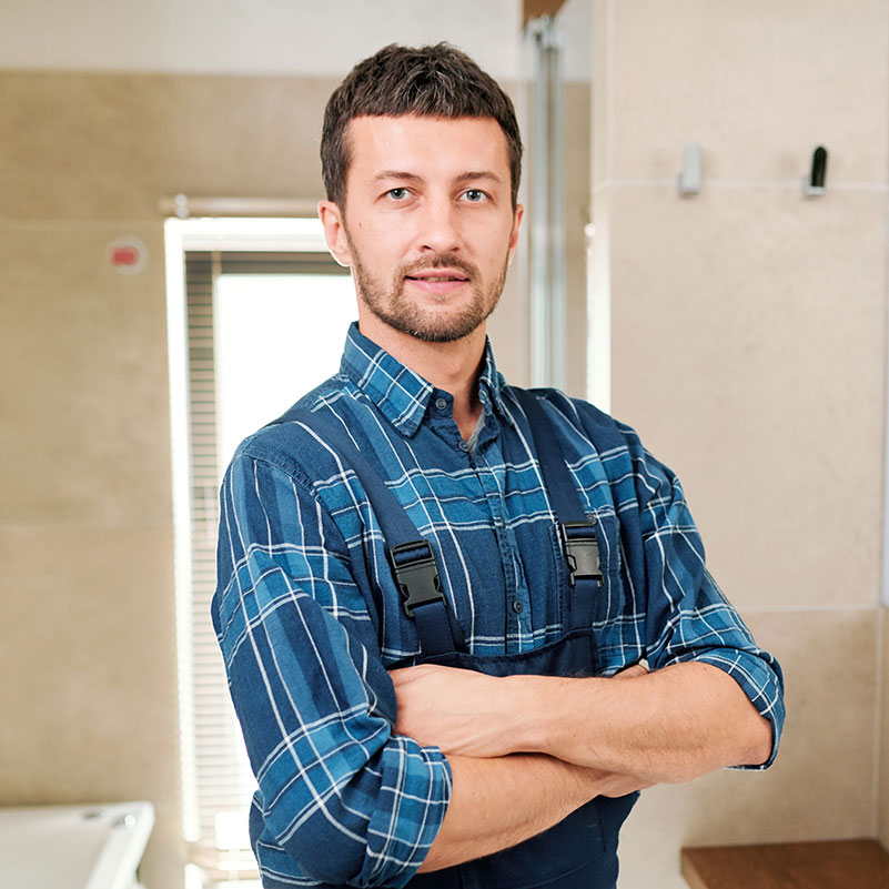 young-successful-plumber-in-workwear-standing-in-b-3P7U6YB