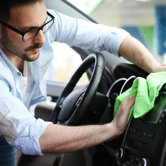 Person cleaning automobile with microfiber clot and maintaining shine