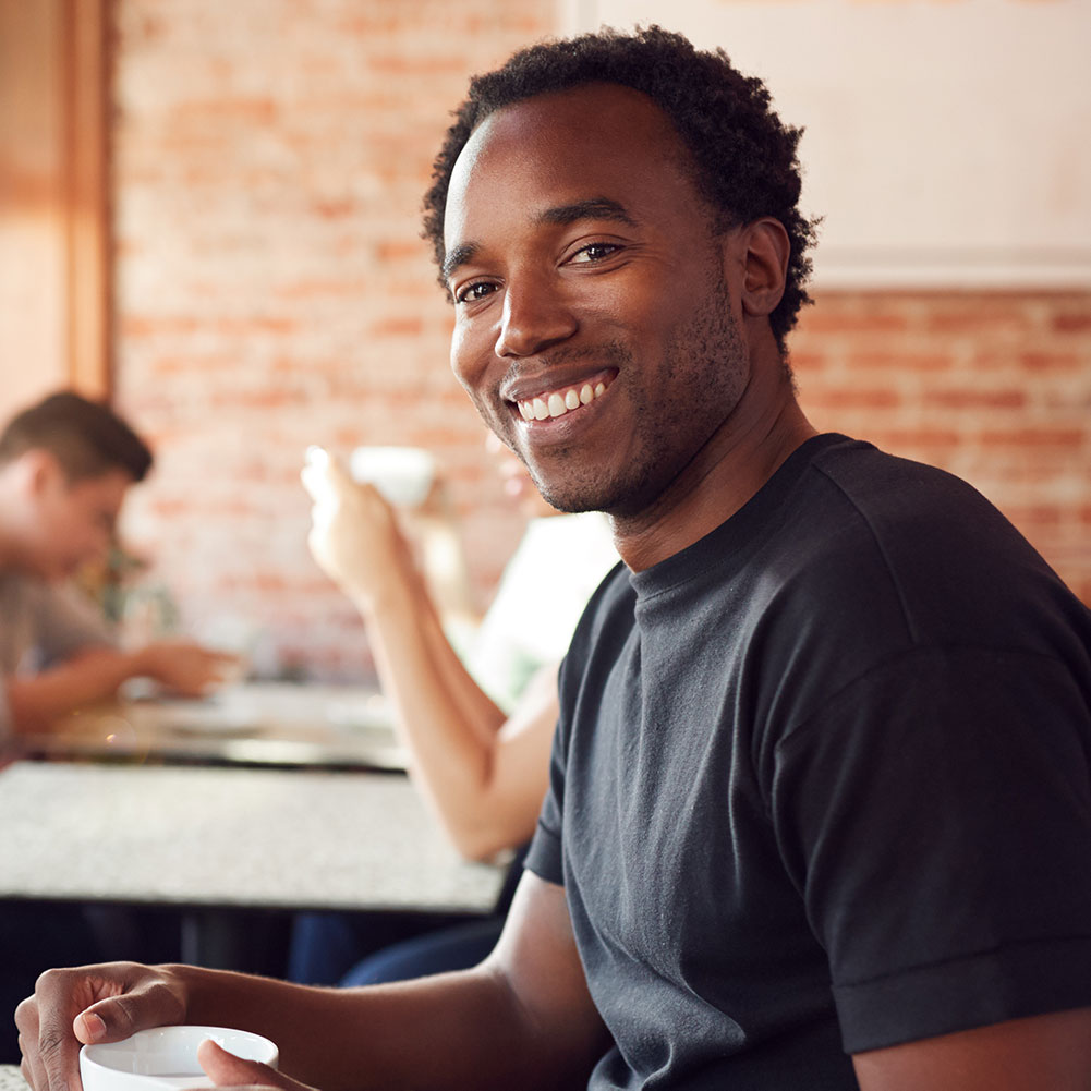 portrait-of-smiling-man-sitting-at-table-in-coffee-X7YY6PU