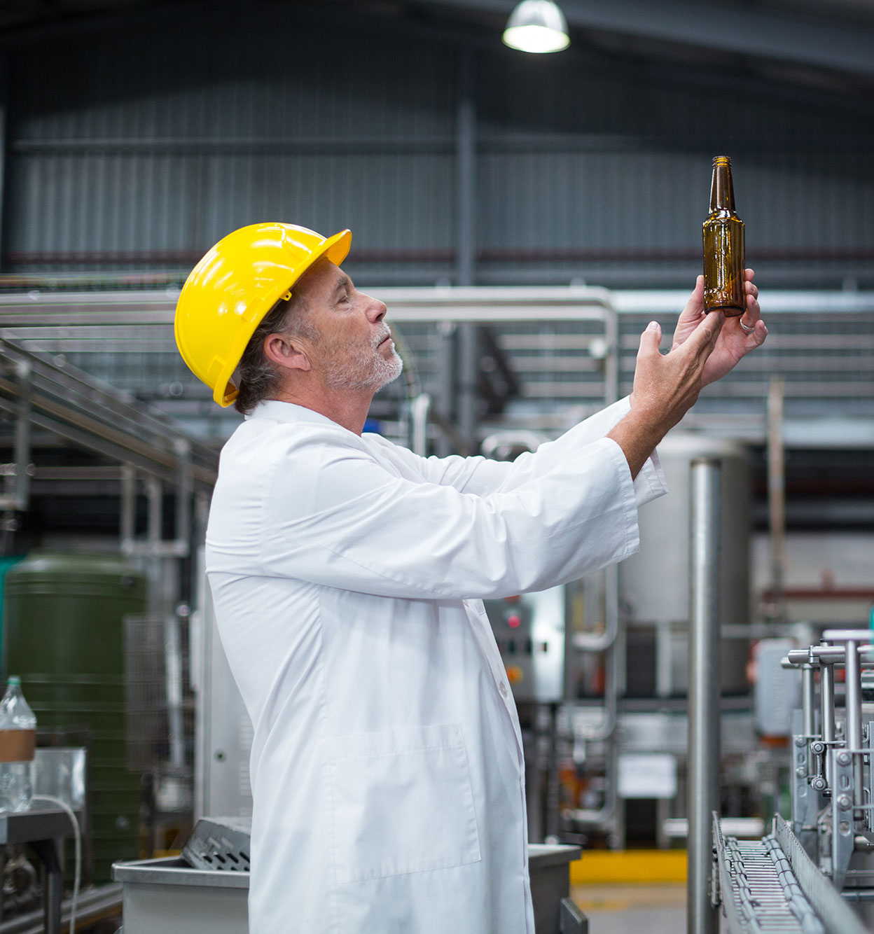 factory-worker-examining-a-bottle-in-factory-A38VZS9-2