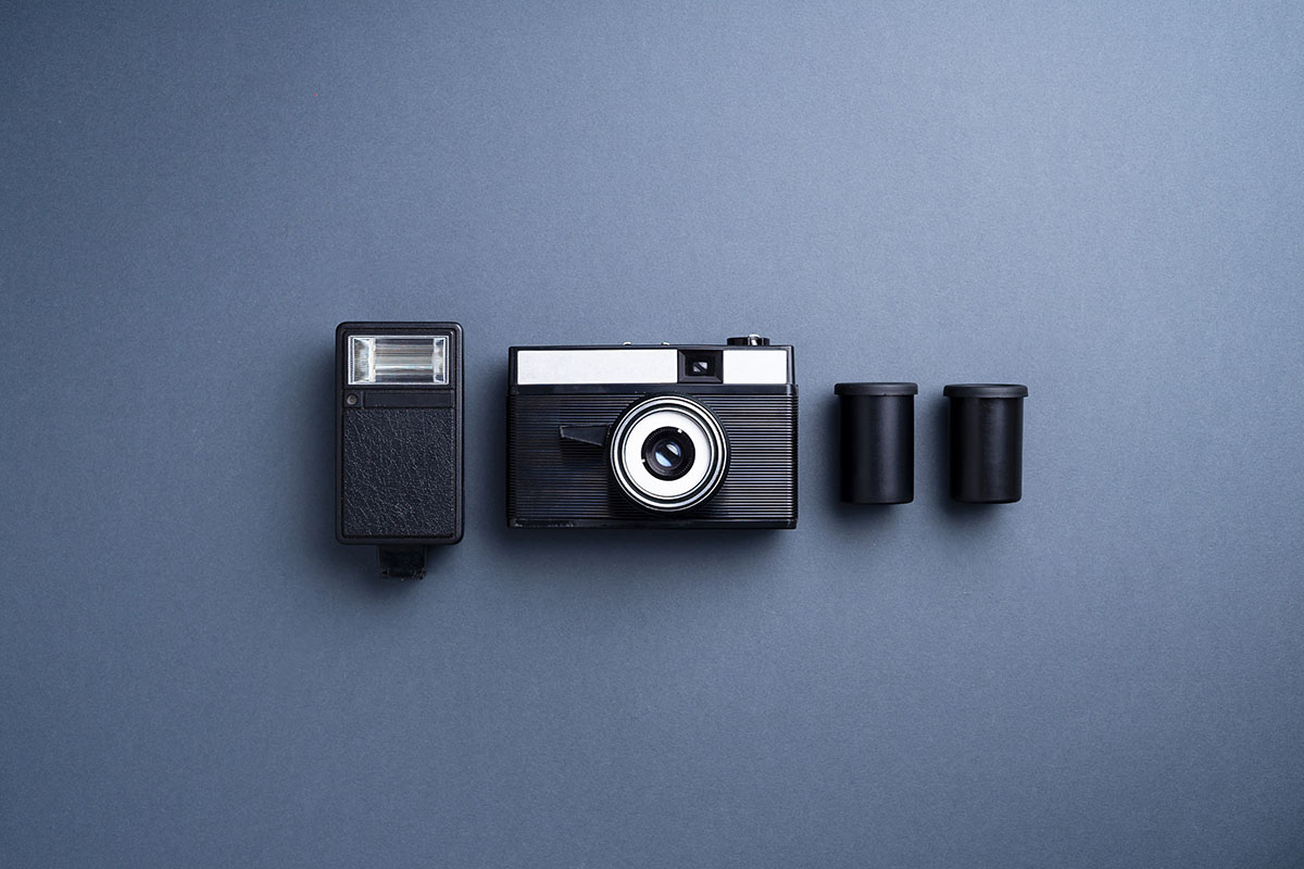 Analog camera and other accessories over gray background
