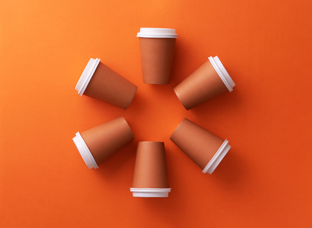 Multiple disposable coffee cups organized in a circle orange background