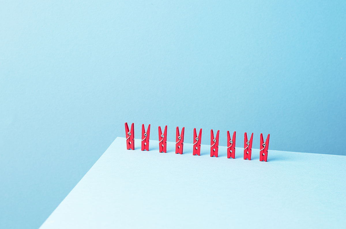 Red laundry clips organized in a row over blue background
