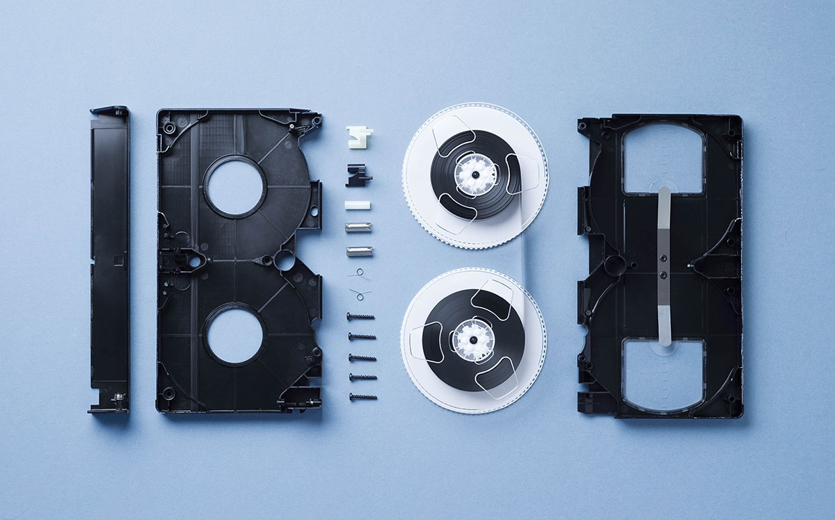 Components of a VHS Cassette disassembled and well arranged over blue background