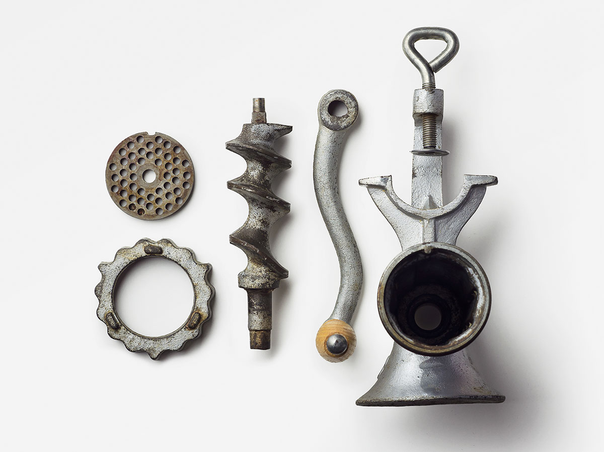 Metal meat grinder well arranged over white background, above view