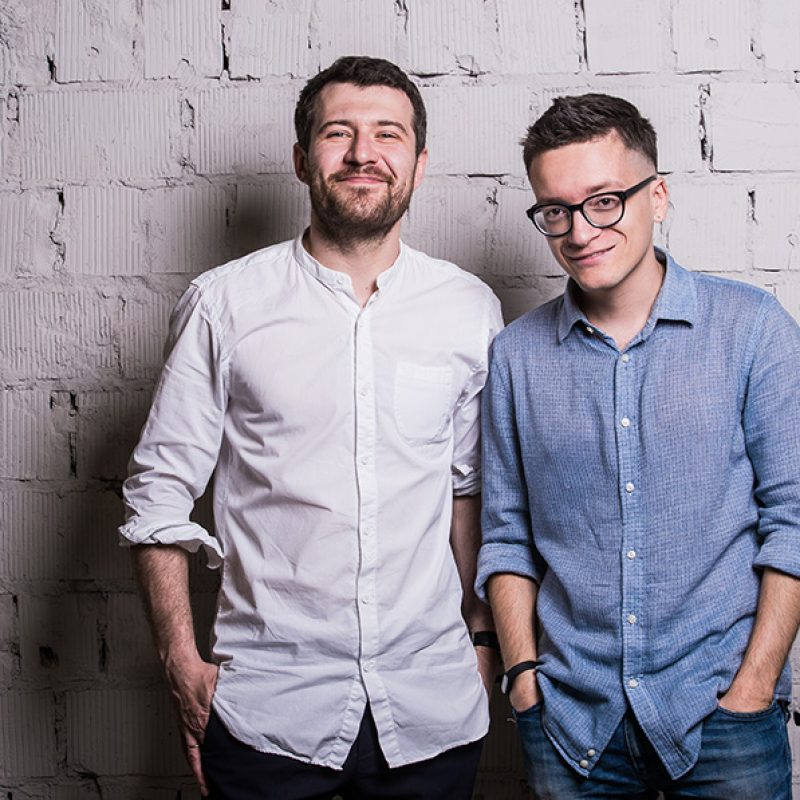 two-young-men-startupers-over-grey-brick-wall-PCL69T8