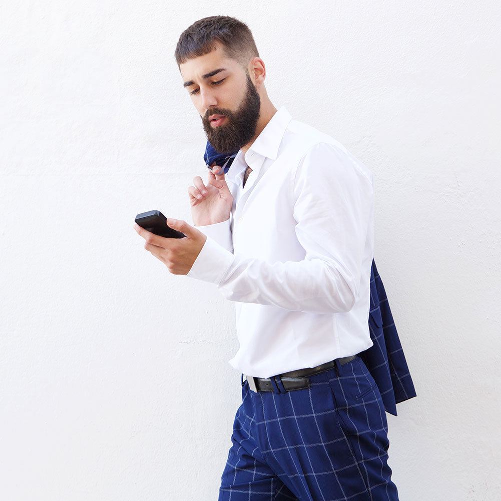 serious-businessman-walking-with-cellphone-and-hol-UABJXKP